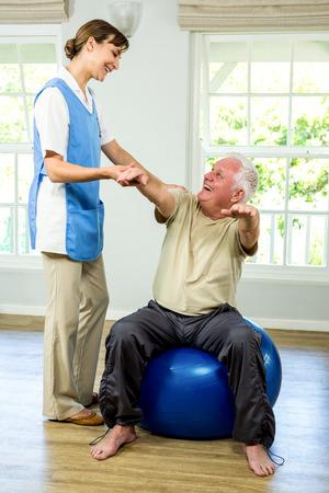 Happy senior man being examined by nurse at health club