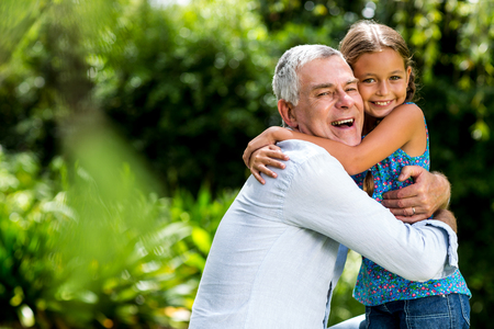 grandaughter: Happy grandfather hugging grandaughter at yard Stock Photo