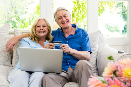 smart card: Portrait of happy senior couple holding smart card with laptop while sitting at home