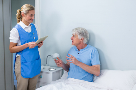 keep watch over: Smiling nurse holding digital tablet while interacting with senior man at hospital
