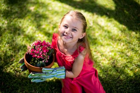 girl holding flower: High angle portrait of smiling girl holding flower pot in yard
