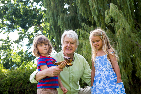 front  or back  yard: Grandfather playing with grandchildren at back yard Stock Photo