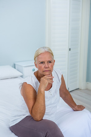 desolaci�n: Upset senior woman with hand on chin sitting on bed in bedroom