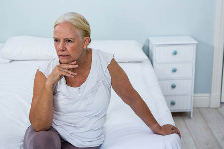dreariness: High angle view of upset senior woman sitting on bed in bedroom