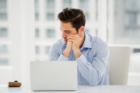 tensed: Tensed businessman sitting at table with laptop in office