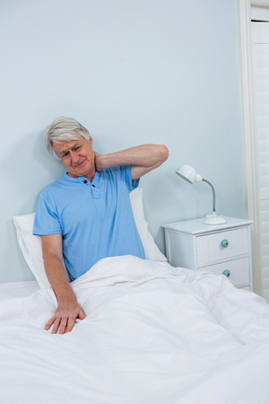 seniors suffering painful illness: Senior man having neck pain while sitting on bed at home
