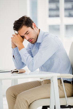 tensed: Tensed businessman sitting at table in office
