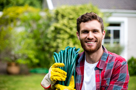 Smiling man carrying garden hose while standing in backyard Stock Photo