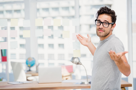 Man shrugging his shoulder in office to say I do not know Stock Photo