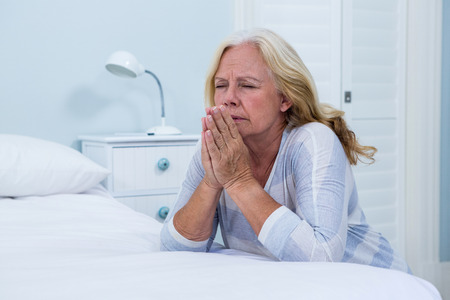Senior woman praying in bedroom at home Stock Photo