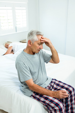 Senior man suffering from headache with woman sleeping on bed at home
