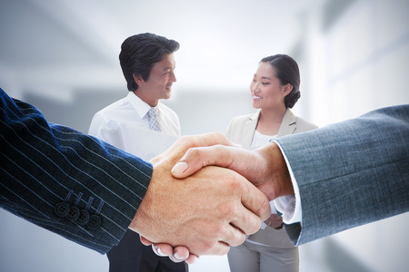 japanese people: Composite image of business people shaking hands in a office