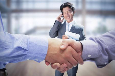men shaking hands: Composite image of two men shaking hands in office