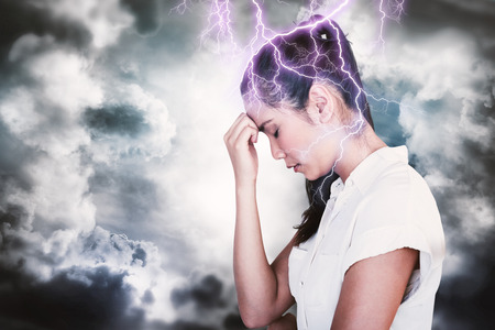 head bowed: Casual upset businesswoman with head bowed against dark sky with white clouds