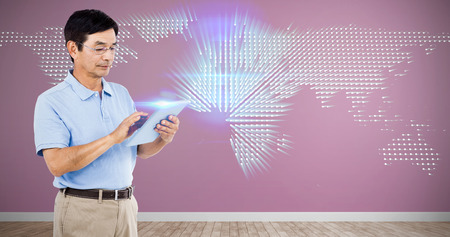 Man using digital tablet while standing against glowing world map on black background Stock Photo