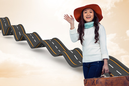 Asian woman with hat holding luggage  against orange vignette