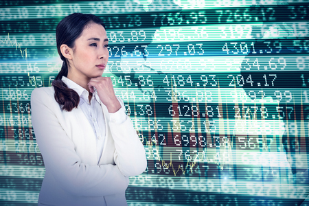 chin: Asian businesswoman touching her chin against stocks and shares