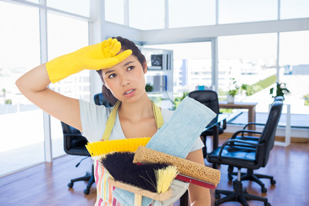 weary: Weary woman holding cleaning tools against board room