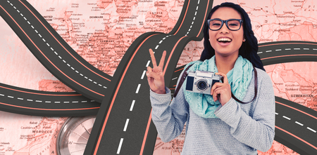 pre adult: Asian woman holding digital camera and making peace sign with hand against world map with compass showing europe and the middle east Stock Photo