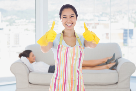 rubber gloves: Happy woman giving thumbs up in rubber gloves against smiling business woman lying down on the couch Stock Photo