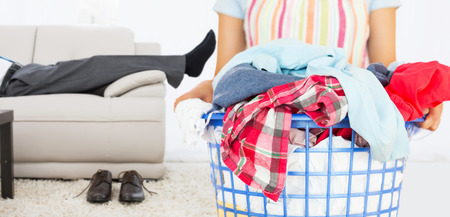 laundry basket: Full laundry basket against low section of a businessman resting on sofa in living room Stock Photo