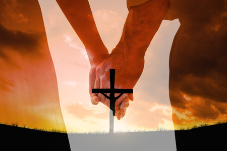 Bride and groom holding hands close up against cross religion symbol shape over sunset sky Фото со стока