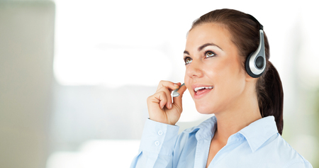 looking upwards: Call center agent looking upwards while talking against steaming cup of coffee Stock Photo