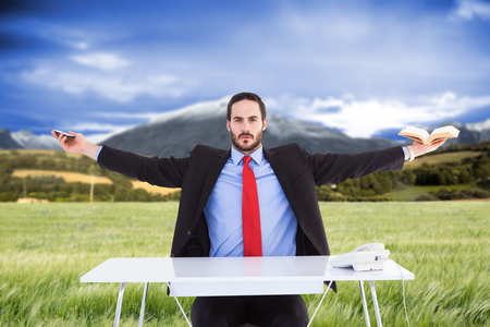 unsmiling: Unsmiling businessman sitting with arms outstretched against scenic backdrop