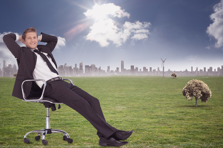 swivel: Businessman relaxing in swivel chair against cityscape on the horizon