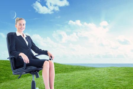 swivel chair: Businesswoman sitting on swivel chair in black suit against green field under blue sky