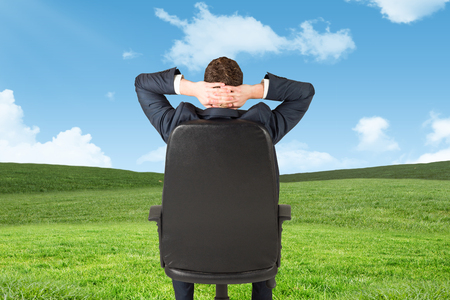 swivel: Businessman sitting in swivel chair  against blue sky over green field Stock Photo