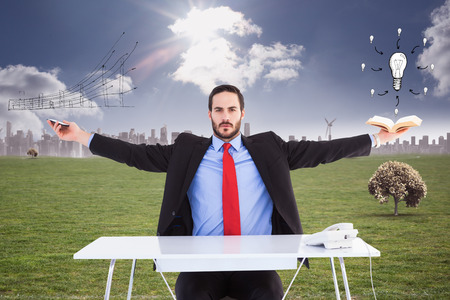 technology career: Unsmiling businessman sitting with arms outstretched against cityscape on the horizon Stock Photo