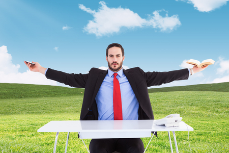 unsmiling: Unsmiling businessman sitting with arms outstretched against blue sky over green field Stock Photo