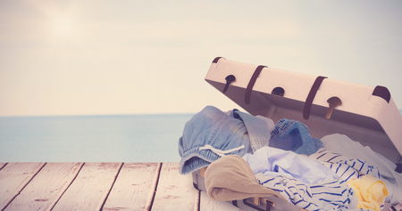 unfolded: Composite image of unfolded clothes against water edge at the beach Stock Photo