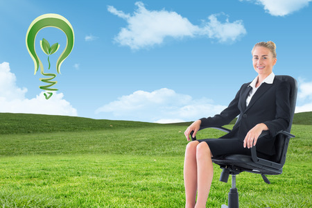 swivel chair: Businesswoman sitting on swivel chair in black suit against blue sky over green field