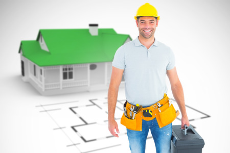 mid distance: Portrait of smiling handyman holding toolbox against blue house behind an architectural plan Stock Photo