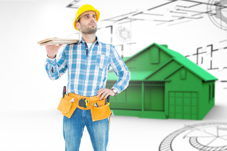 Thoughtful worker carrying wooden planks against big house in grey with architect plans