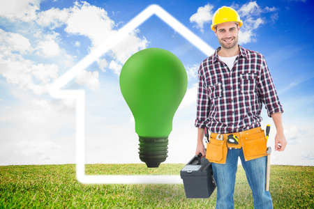 green light bulb: Happy male hanyman carrying toolbox against green light bulb with white house outline