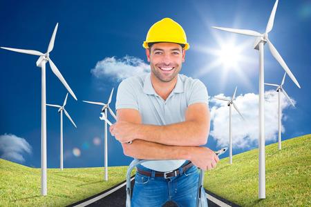 llave de sol: Manitas con herramientas de mano en escalera de mano contra la carretera que conduce hacia el horizonte con turbinas de viento a cada lado Foto de archivo