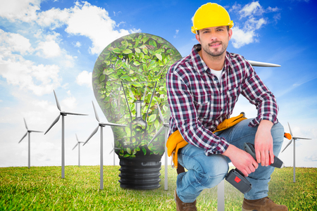 power drill: Crouching handyman holding power drill against wind turbines and bulb full of leaves