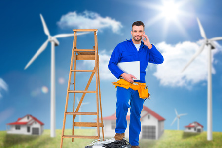 environmental conversation: Carpenter on the phone  against houses in a turbine field Stock Photo