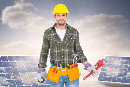 floorboards: Manual worker holding various tools  against solar panels on floorboards in the sky Stock Photo