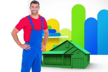 ber: Happy handyman in overalls with hands on hip against house with energy rating background Stock Photo