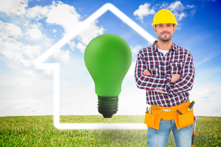 green light bulb: Manual worker standing arms crossed against green light bulb with white house outline Stock Photo