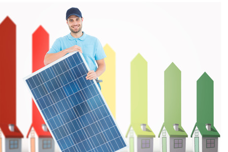representing: Smiling construction worker holding solar panel  against seven 3d houses representing energy efficiency Stock Photo