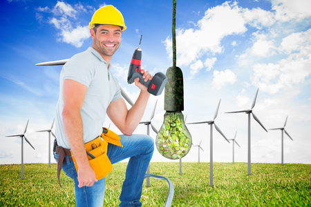 power drill: Confident handyman holding power drill while climbing ladder against renewable and clean energy Stock Photo