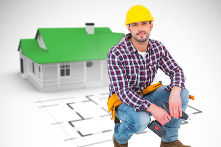 power drill: Crouching handyman holding power drill against blue house behind an architectural plan Stock Photo