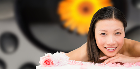 massage  table: Relaxed woman lying on the massage table against orange flower floating in bowl with pebbles Stock Photo