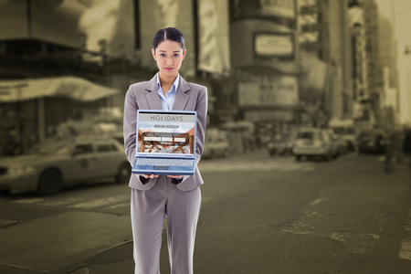 booked: Portrait of a businesswoman showing a notebook against view of a city Stock Photo