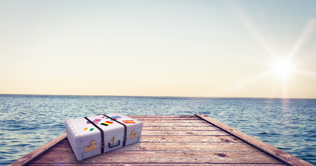 composite image: Composite image of suitcase against beautiful day in the water